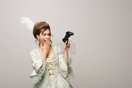Photo for KYIV, UKRAINE - APRIL 22, 2021: shocked, retro style woman holding joystick and covering mouth with hand isolated on grey - Royalty Free Image