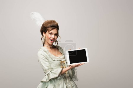 Photo for Amazed vintage style woman showing digital tablet with blank screen isolated on grey - Royalty Free Image