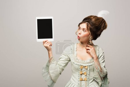 surprised retro style woman looking at digital tablet with blank screen isolated on grey