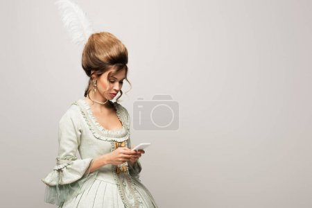 elegant woman in vintage dress messaging on smartphone isolated on grey