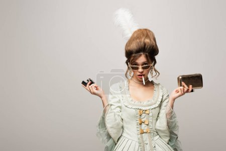 Photo for Young woman in retro outfit holding lighter and golden purse bag while smoking isolated on black - Royalty Free Image