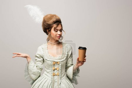 young woman in stylish vintage clothing holding takeaway drink isolated on grey