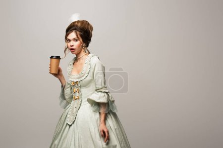 surprised woman in vintage outfit holding paper cup while looking at camera isolated on grey