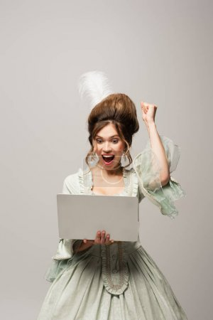excited retro style woman showing triumph gesture while looking at laptop isolated on grey