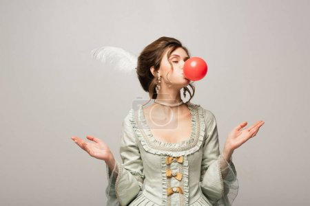 elegant woman in vintage outfit blowing red bubble gum isolated on grey