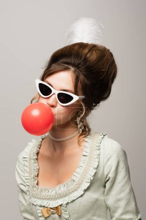 vintage style woman in trendy sunglasses blowing red bubble gum isolated on grey