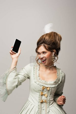 excited retro style woman holding mobile phone with blank screen isolated on grey