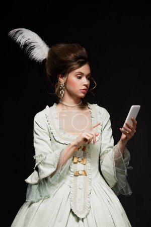 pretty woman in vintage outfit pointing at mobile phone isolated on black