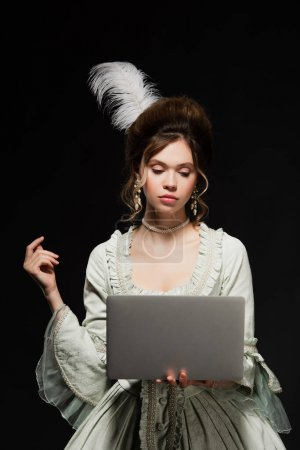 charming woman in elegant vintage outfit looking at laptop isolated on black