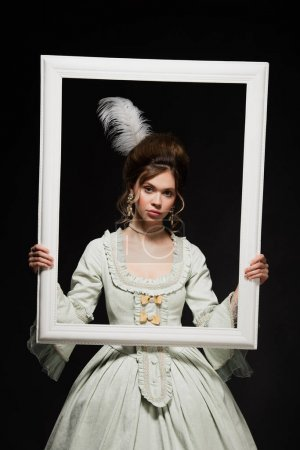 charming woman in elegant vintage outfit holding white framing isolated on black