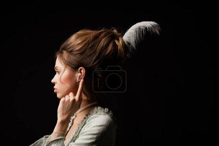 Photo pour Vue latérale de la femme de style rétro pointant vers l'écouteur tout en écoutant de la musique isolée sur noir - image libre de droit