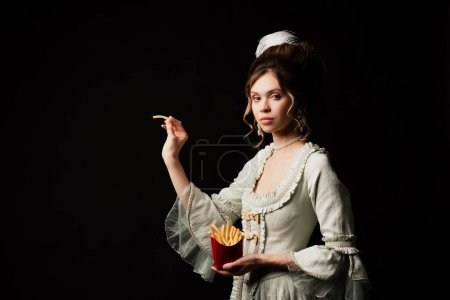 charming woman in vintage pastel grey dress posing with french fries isolated on black