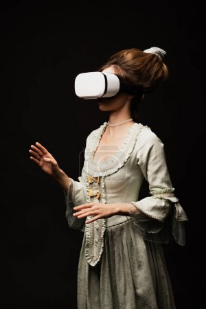 vintage style woman in pastel grey dress gaming in vr headset isolated on black