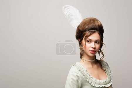 charming woman with retro hairstyle looking away isolated on grey