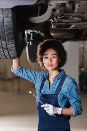 young african american mechanic holding wrench in hand and standing underneath car in garage
