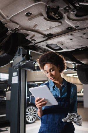 joven afroamericano mecánico en overoles de pie debajo del coche y la celebración de tableta digital en el garaje