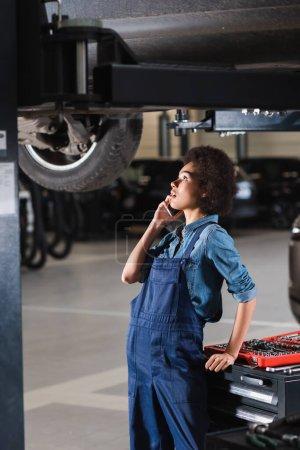 Photo pour Jeune mécanicien afro-américain parlant sur téléphone portable dans le garage - image libre de droit