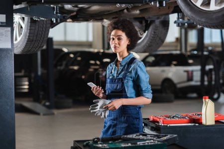 young african american mechanic standing underneath car and holding cellphone in garage