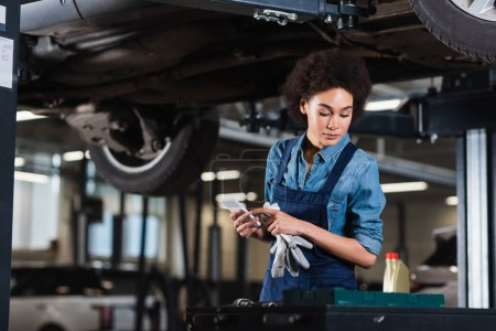 Photo for Young african american mechanic working underneath car and holding cellphone in hand in garage - Royalty Free Image