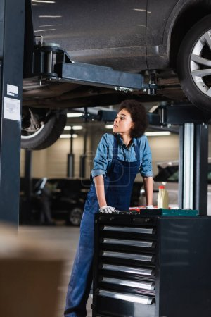 tired young african american mechanic standing underneath car in garage