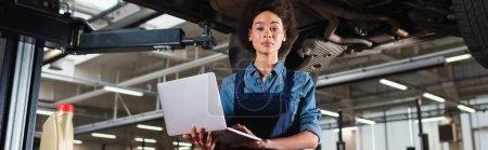 Photo pour Jeune mécanicien afro-américain debout sous la voiture, tenant un ordinateur portable et regardant la caméra dans le garage, bannière - image libre de droit