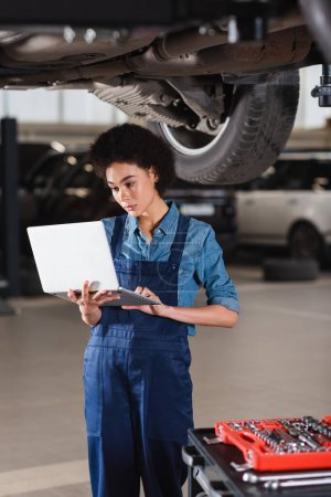 young african american mechanic standing underneath car and typing on laptop in garage
