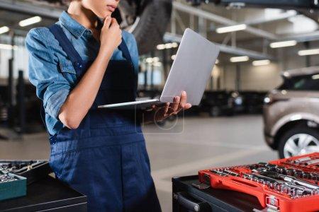 Photo pour Vue partielle du jeune mécanicien afro-américain tenant la main près du visage et regardant l'ordinateur portable dans le garage - image libre de droit