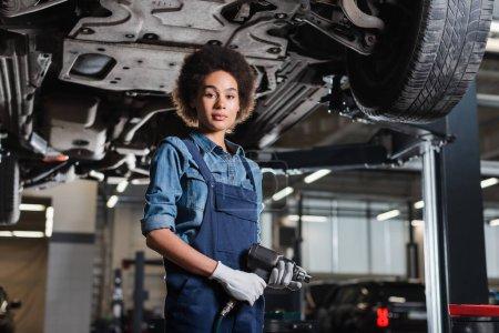 joven afroamericano mecánico en overoles de pie con destornillador eléctrico debajo del coche levantado en el garaje