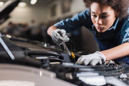 Photo pour Jeune mécanicien afro-américain travaillant avec moteur de voiture dans le garage - image libre de droit