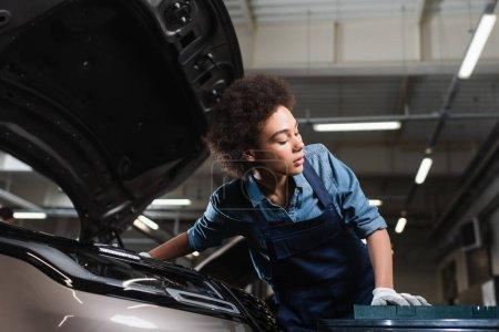 Photo pour Jeune mécanicien afro-américain fixation moteur de voiture dans le garage - image libre de droit