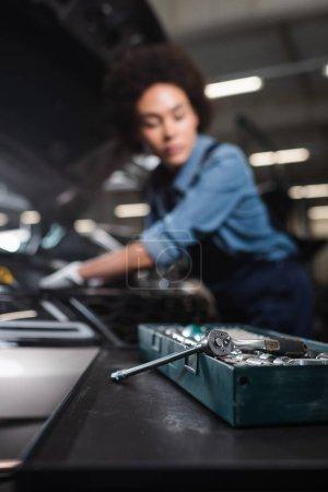 Photo pour Vue rapprochée de la clé dans la boîte à outils avec un mécanicien afro-américain flou travaillant avec une voiture dans le garage - image libre de droit