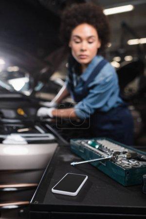 Photo pour Vue rapprochée du téléphone portable et clé à outils dans la boîte à outils avec femme afro-américaine floue travaillant dans le garage - image libre de droit