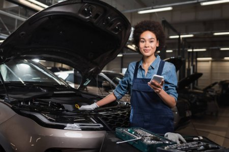 smiling young african american mechanic standing with cellphone near car with open hood in garage