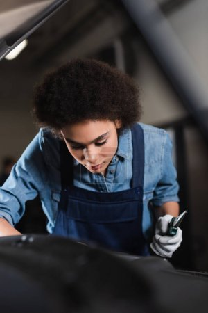 Photo for Young african american mechanic holding pliers and working with motor of car in garage - Royalty Free Image