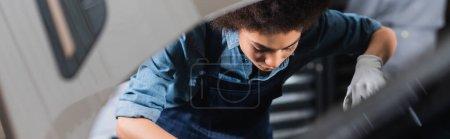 Photo pour Jeune mécanicien afro-américain en salopette travaillant avec capuche de voiture dans le garage, bannière - image libre de droit