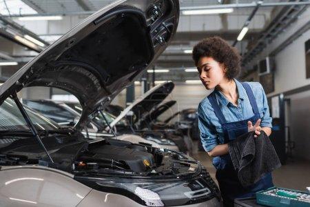 Photo pour Jeune mécanicien afro-américain sèche-mains avec serviette près de la voiture avec capuche ouverte dans le garage - image libre de droit