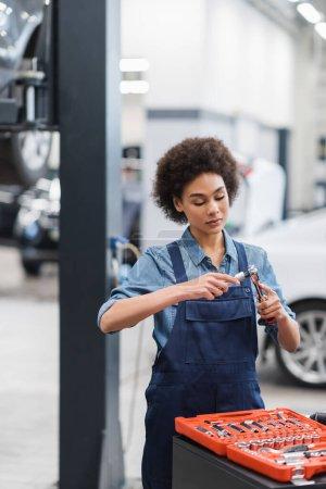 Photo pour Jeune mécanicien afro-américain tenant l'équipement dans le garage de réparation automobile - image libre de droit