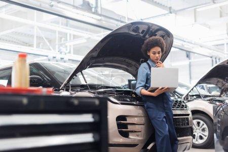 joven africano americano mecánico celebración portátil cerca de coche con capucha abierta en el servicio de reparación de automóviles
