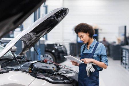 Photo pour Jeune mécanicien afro-américain tenant tablette numérique près de la voiture avec capuche ouverte dans le service de réparation automobile - image libre de droit