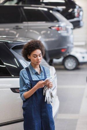 joven afroamericano mecánico en overoles escribiendo en smartphone en garaje