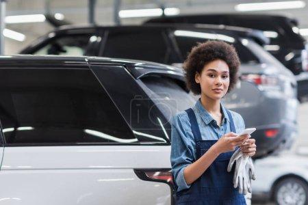 Photo pour Positif jeune mécanicien afro-américain en salopette debout avec smartphone dans le service de réparation automobile - image libre de droit