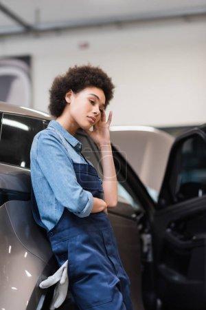 Photo pour Bouleversé jeune mécanicien afro-américain debout avec la main près du visage dans le service de réparation automobile - image libre de droit