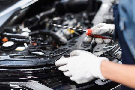 Photo pour Vue rapprochée des mains mécaniques féminines dans des gants réparer moteur de voiture avec tournevis dans le garage - image libre de droit