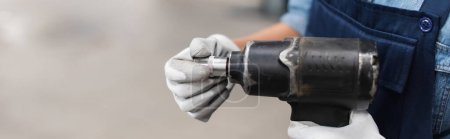 close up view of mechanic hands in gloves holding electric screwdriver and attachment on blurred background, banner