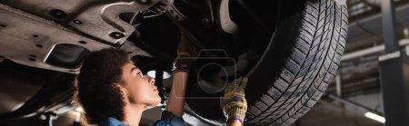 Photo pour Jeune mécanicien afro-américain réparer roue de voiture soulevée dans le garage, bannière - image libre de droit