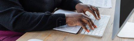 vista parcial de la mujer de negocios afroamericana escribiendo en el teclado de la computadora en la oficina, bandera