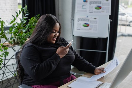 Photo for Happy african american plus size businesswoman taking photo of documents on smartphone in office - Royalty Free Image