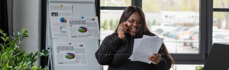 Photo for Cheerful african american plus size businesswoman talking on smartphone and holding documents, banner - Royalty Free Image