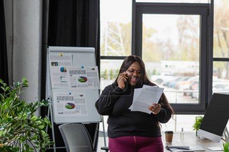 feliz afroamericana más tamaño mujer de negocios hablando en el teléfono inteligente y la celebración de documentos