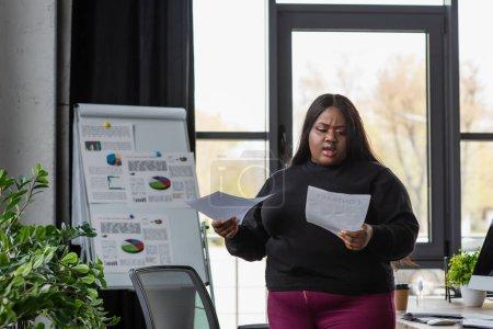 Afrikanisch-amerikanische Plus-Size-Unternehmerin schaut sich Dokumente an